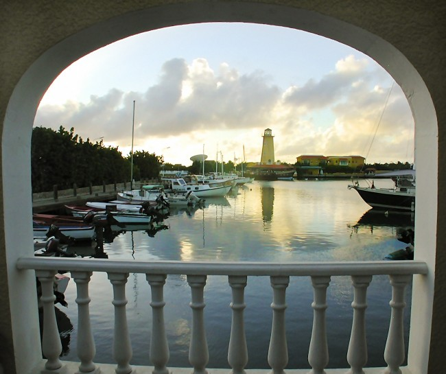 We look through a window cut away across a harbor at a lighthouse, the sun is setting on the Island of Bonaire.