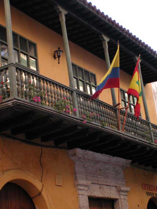A shot of a beautiful tan balcony flying traditional Colombian flags.