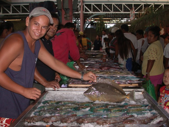 A young man tend to his catch at the fish market Papeete